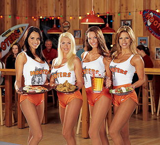 "Four Hooters employees are pictured standing side by side. Three of them are holding plates of food and the other is holding a pitcher of beer. Each of them is wearing a white tank top that says ""Hooters,"" and high cut shorts."