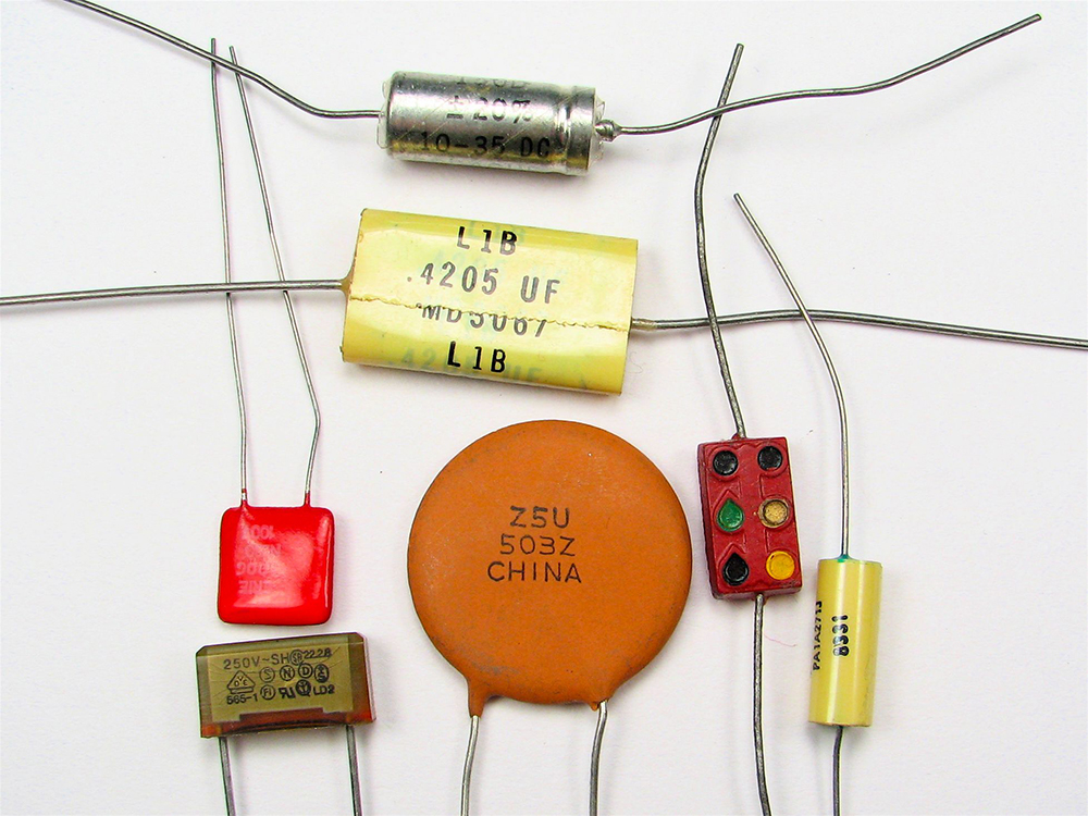 There are various types of capacitors with varying shapes and color. Some are cylindrical in shape, some circular in shape, some rectangular in shape, with two strands of wire coming out of each.