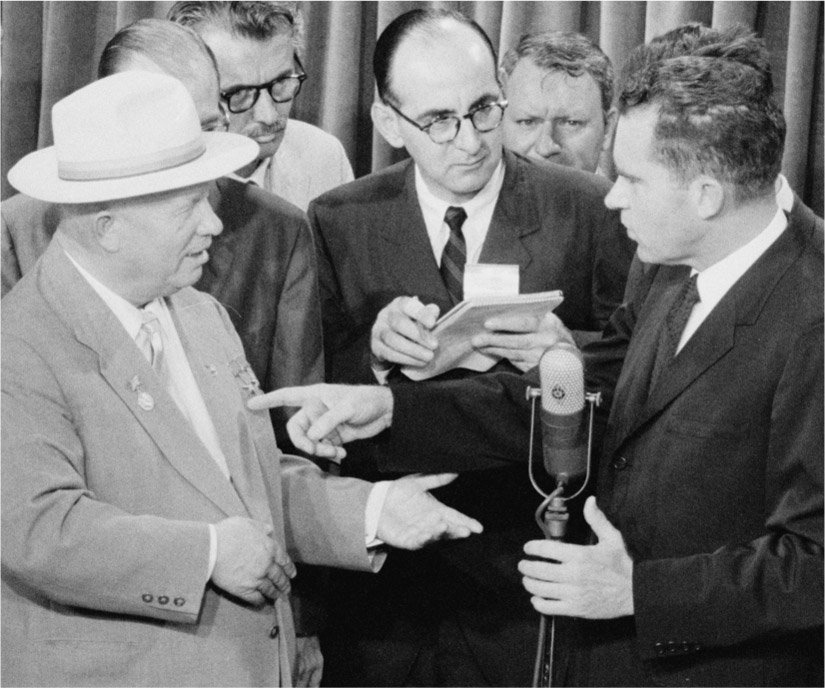 Nikita Khrushchev and Richard Nixon talk into a microphone and point to each other. Reporters stand closely around them.