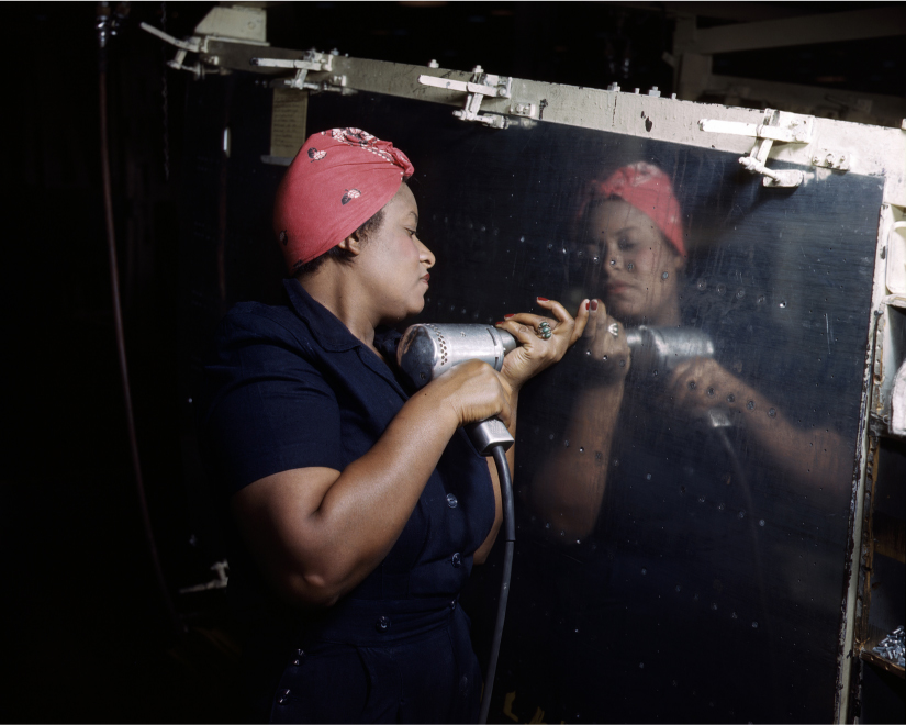A woman uses a hand drill to work on an A-31 Vengeance dive bomber.