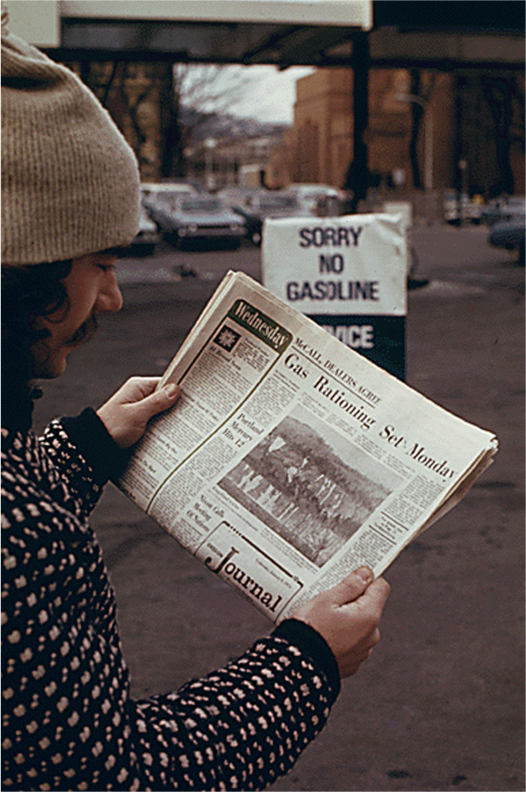 A man holds a newspaper that reads