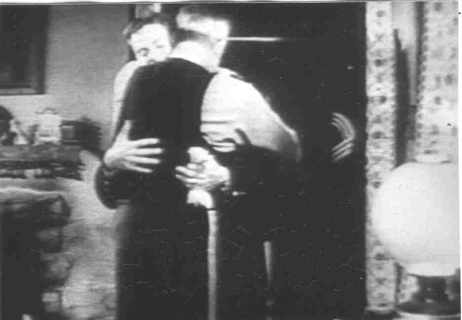 A film screenshot of two men embracing inside a home.