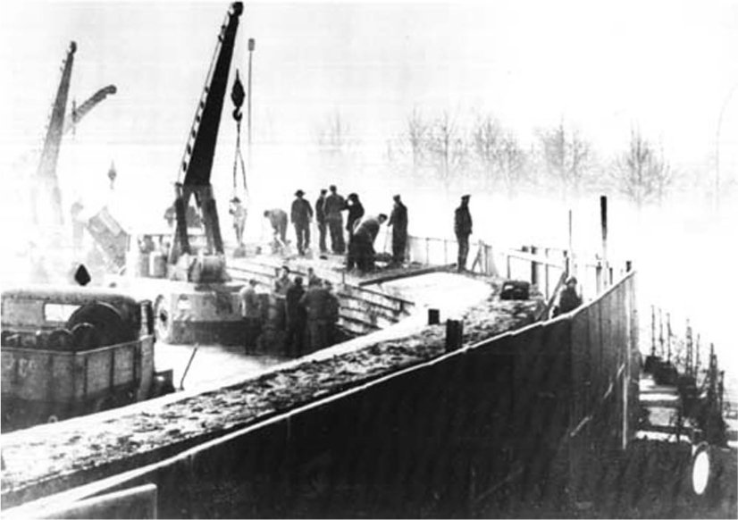 Men work on top of a wide, tall wall. Cranes are on the left side of the wall. Two fences surround the wall on the right side.