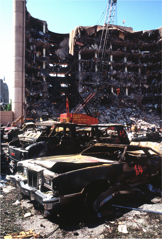 Damaged automobiles surrounded by debris are in the foreground. A building covered in debris is in the background. A crane is in front of it.