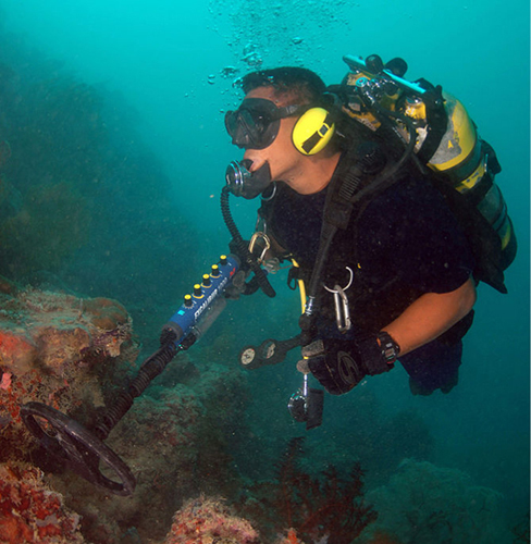 Photograph of an underwater diver using a metal detector.