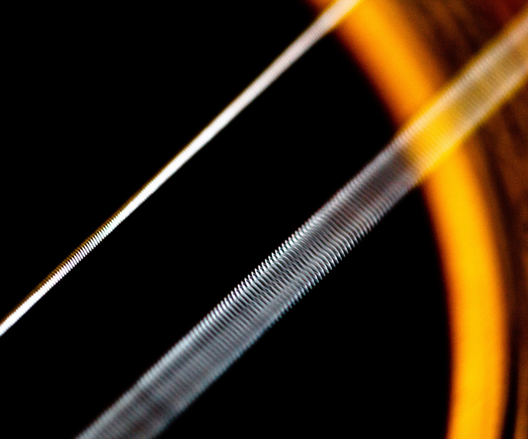The given figure shows a closed zoom view of the strings of a guitar. There are two slanting white colored strings in the picture. In the nearer string, the gaps between the circular threads of the string are visible, whereas the second white string at the back looks like a white thin stick.