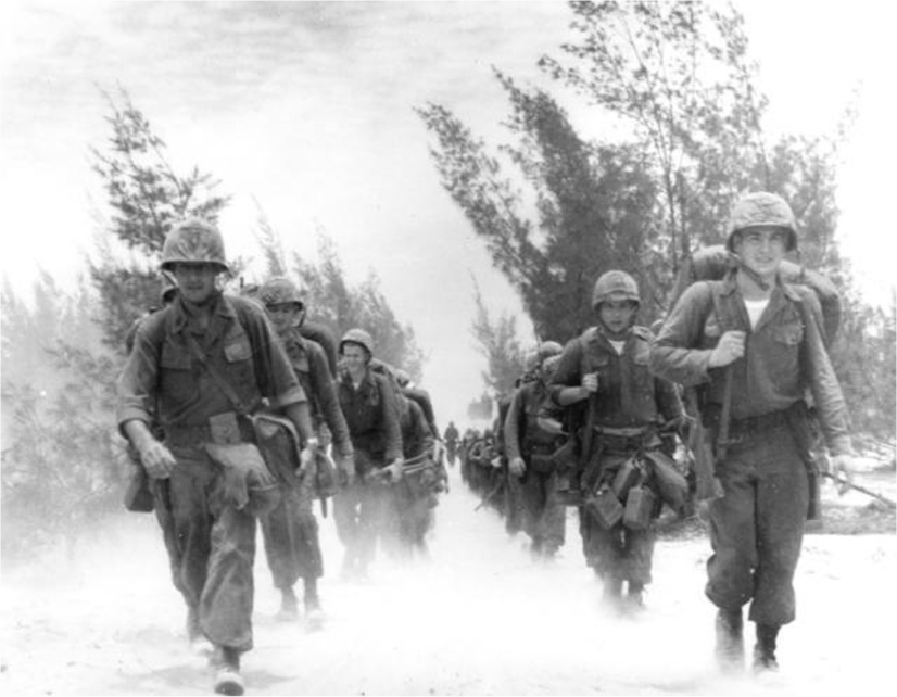 Two rows of U.S. Marines march down a road.