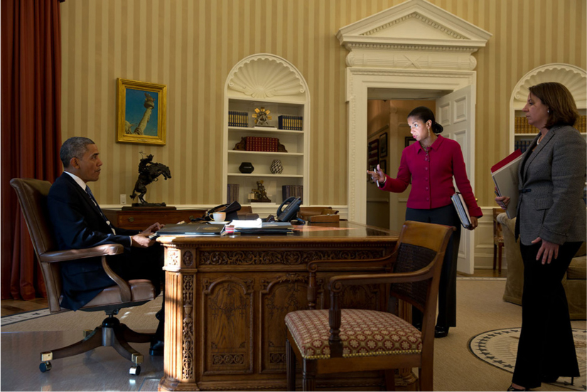 President Obama sits behind his desk in the Oval Office. Two women stand on the other side of the desk and talk to the President.