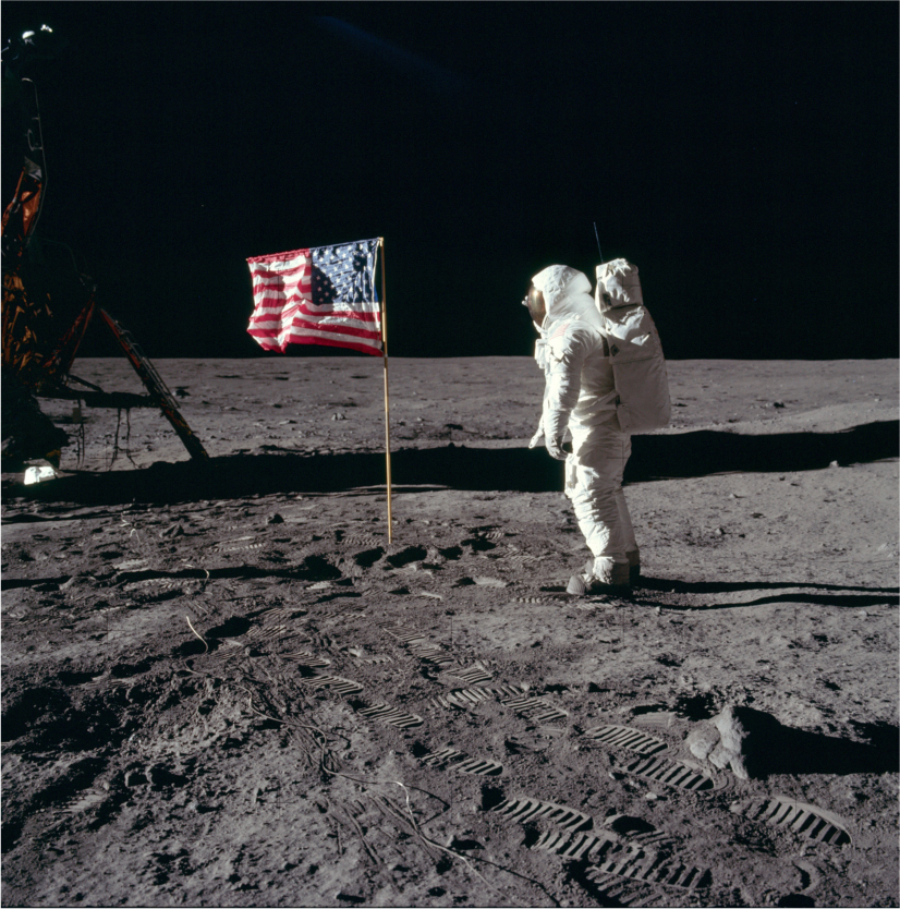 Buzz Aldrin stands on the moon and salutes the American flag that is planted on the surface of the moon.