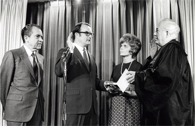 William Ruckelshaus raises his right hand resting his left hand on the Bible and looks at the judge in front of him. His wife Jill Ruckelshaus stands in between them holding the Bible. President Nixon stands next to William Ruckelshaus.