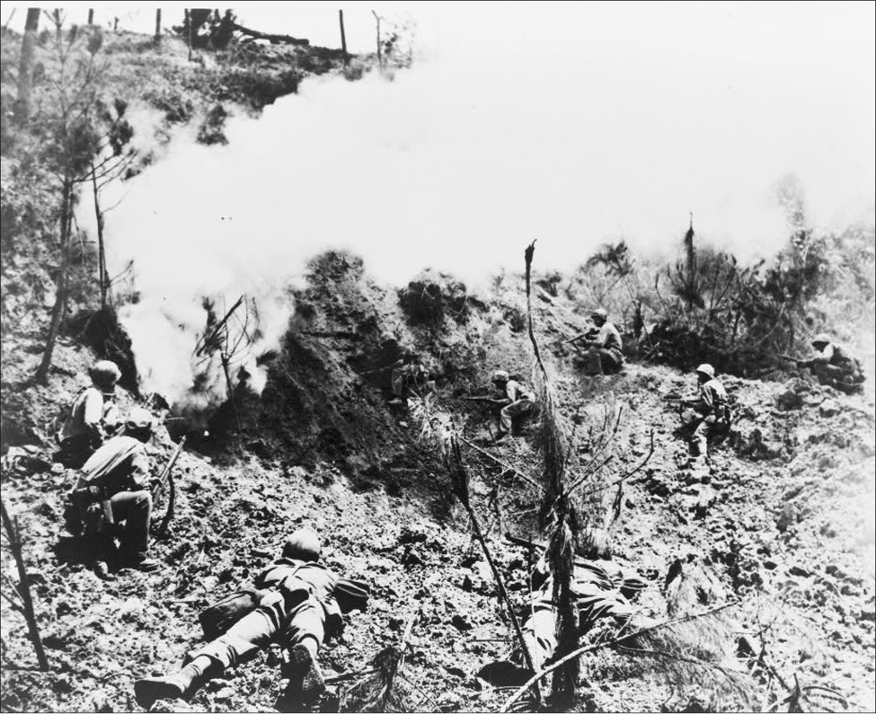 Multiple soldiers lie or crouch on the ground, aiming their rifles at a cave. Smoke comes out of the cave.
