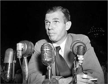 Alger Hiss sitting behind multiple microphones.