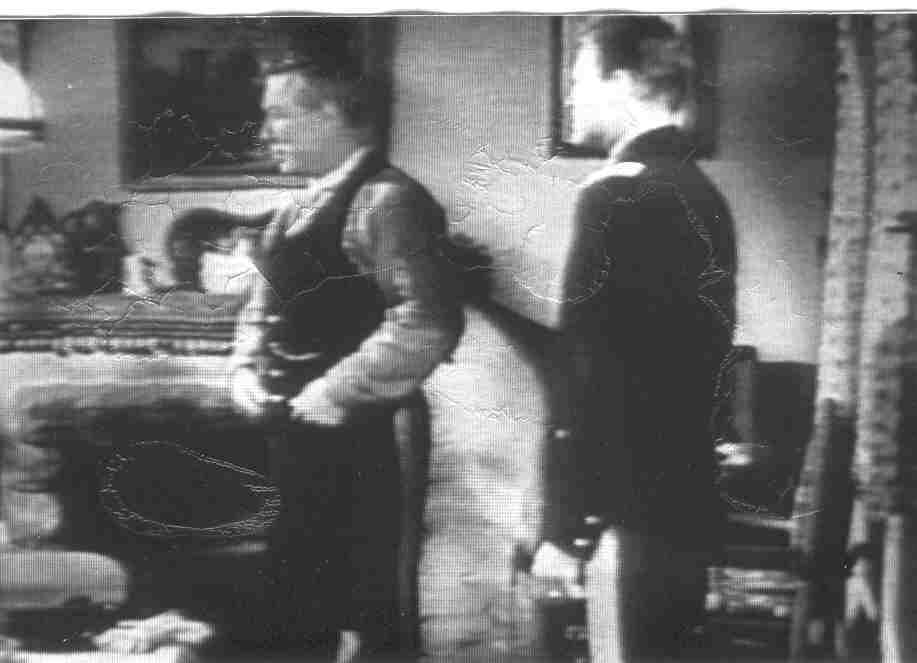 A film screenshot of two men engaging in conversation in front of the hearth of a home.