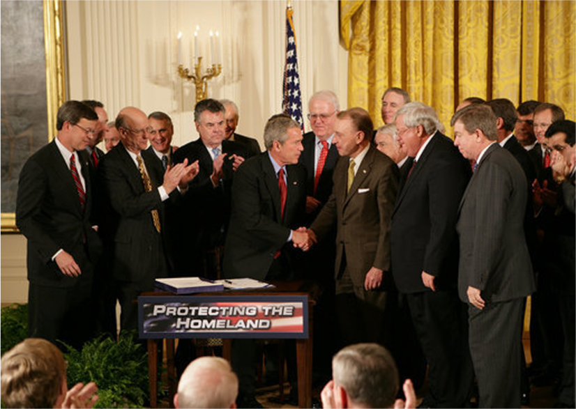 President George W. Bush shakes hands with a senator behind a podium that says