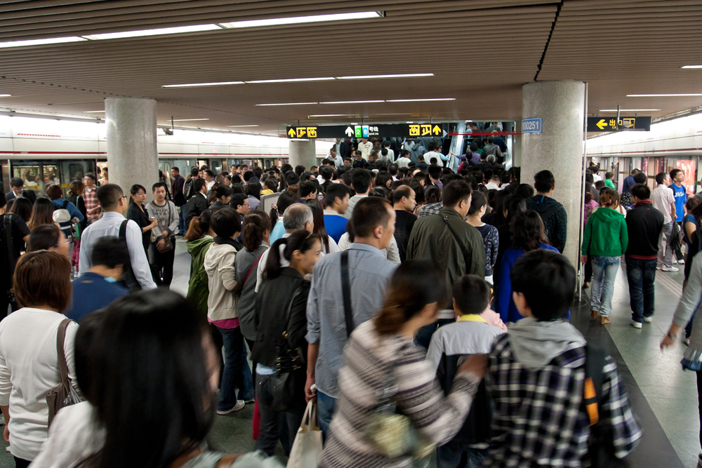 People walking around a crowded subway station are shown here