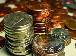 A photo of coins; separate stacks of nickels, pennies, quarters, and dimes