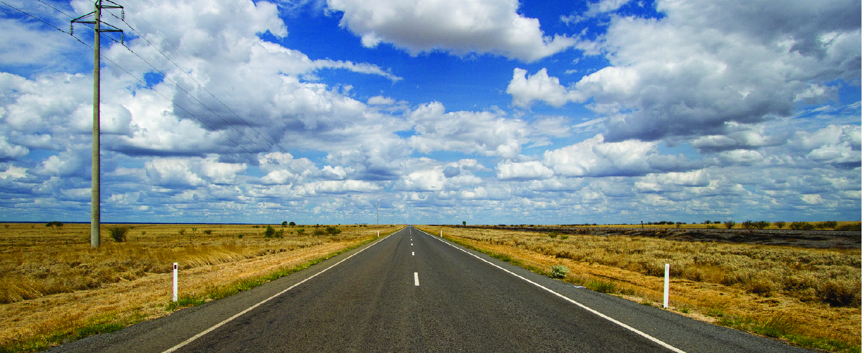 This image looks down the middle of an open road with clouds in the sky and open landscape on either side of the road.