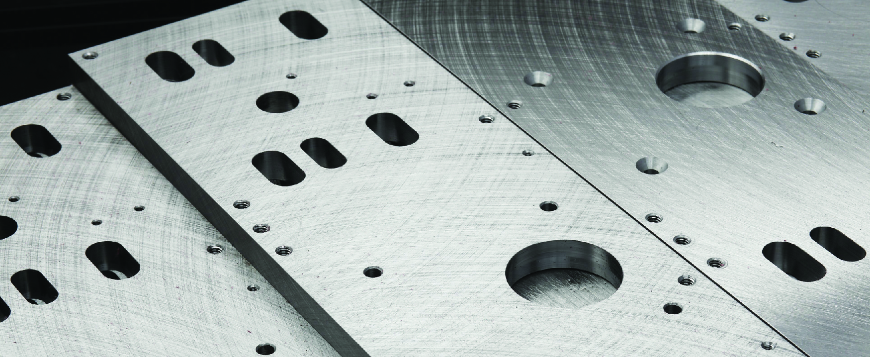 A picture of precision machined metal plates with many holes of differing sizes.