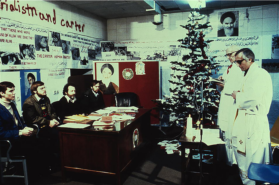 American hostages sit at a table in front of a wall filled with photographs and writing such as