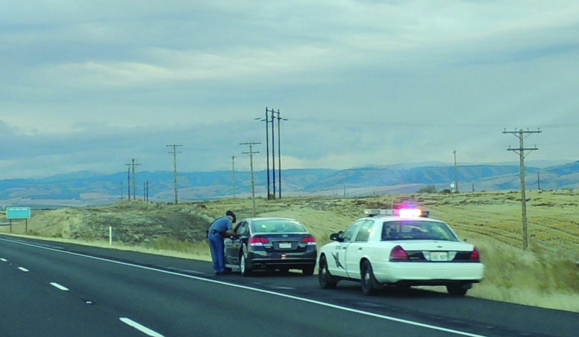 A photo of two cars on the side of a paved road. One car is a police car and has flashing lights on top. In front of the police car is another vehicle. An officer stands by the side of that vehicle.