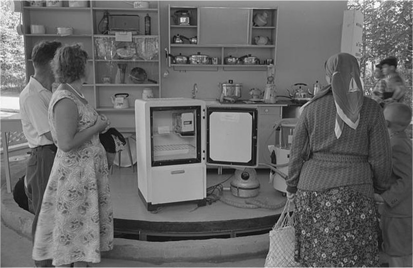 A group of people look at an exhibit of a kitchen that includes a refrigerator
