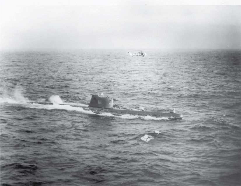 A submarine surfaces, and a helicopter flies above it.