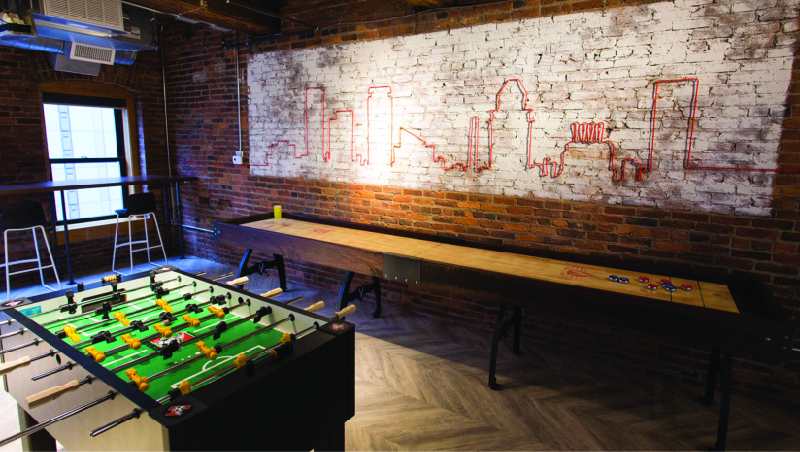 This image shows a room with a shuffleboard table and a foosball table.