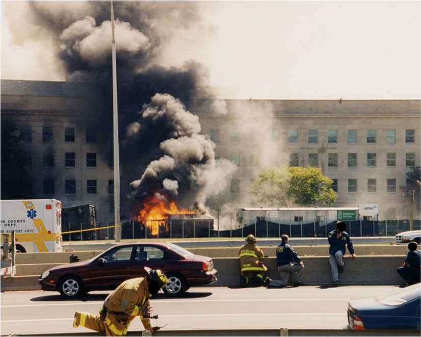 Firefighters crouch across the street from the Pentagon, which is on fire. Black smoke rises from the flames in front of the Pentagon.
