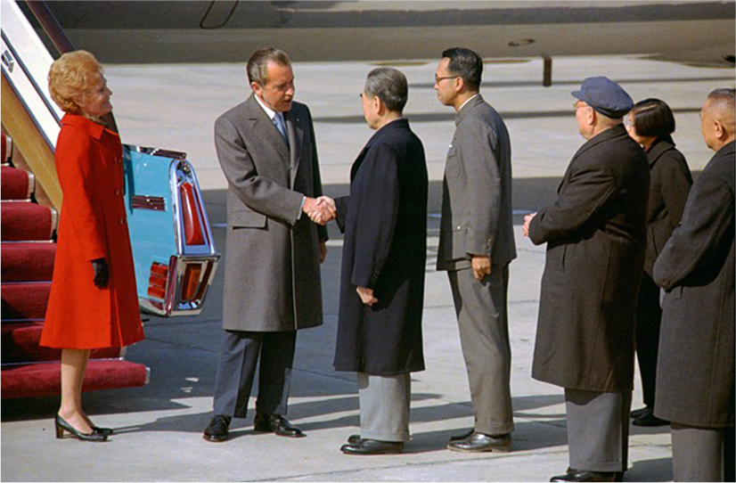 President Nixon and Premier Zhou Enlai shake hands in front of an airplane staircase. Nixon's wife, Pat, and Chinese leaders look on.