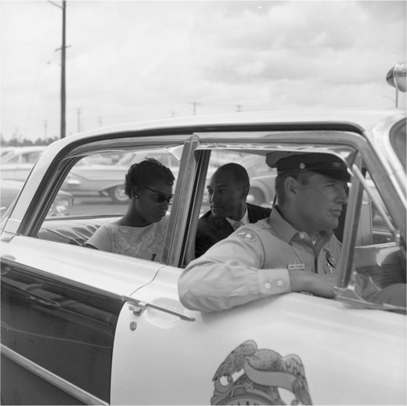 Two African Americans ride in the backseat of a police car.