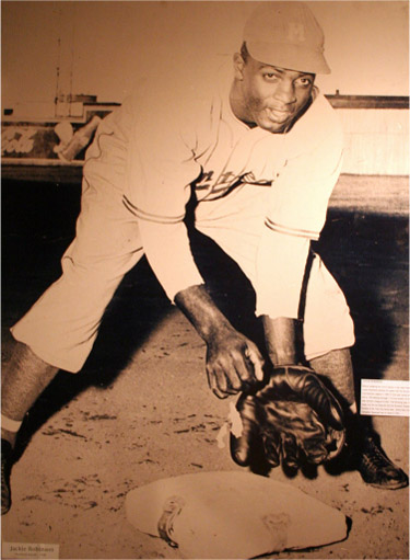 Jackie Robinson crouches over a base to catch a baseball.