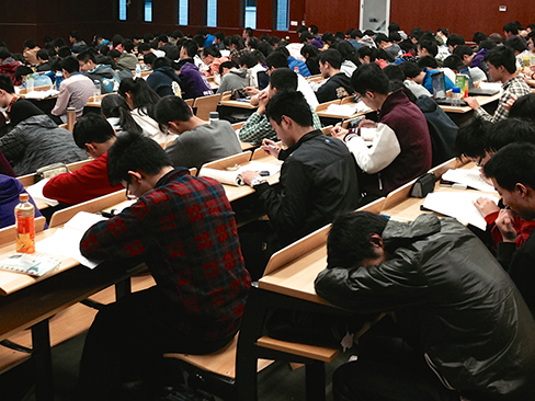 Many students studying in a large lecture hall