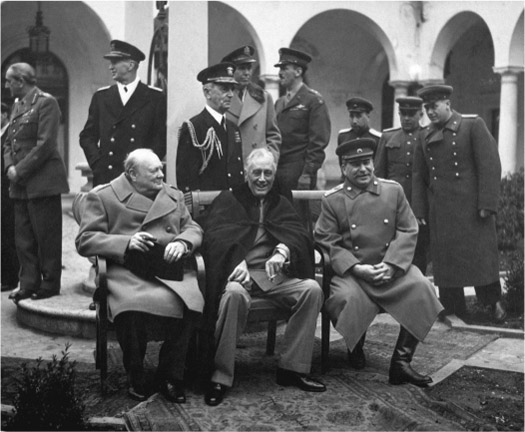 Smiling, Winston Churchill, Franklin Roosevelt, and Joseph Stalin sit on a bench in a courtyard. Men in various uniforms stand behind them.