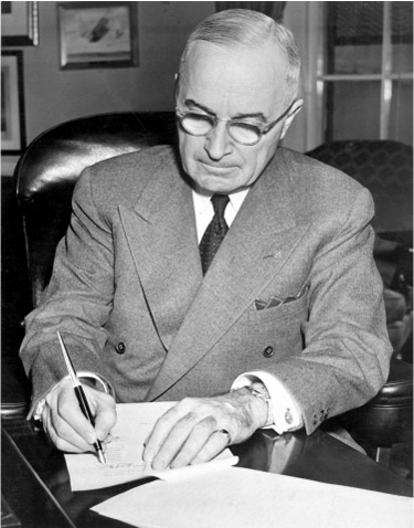 President Truman signs a document at a desk.