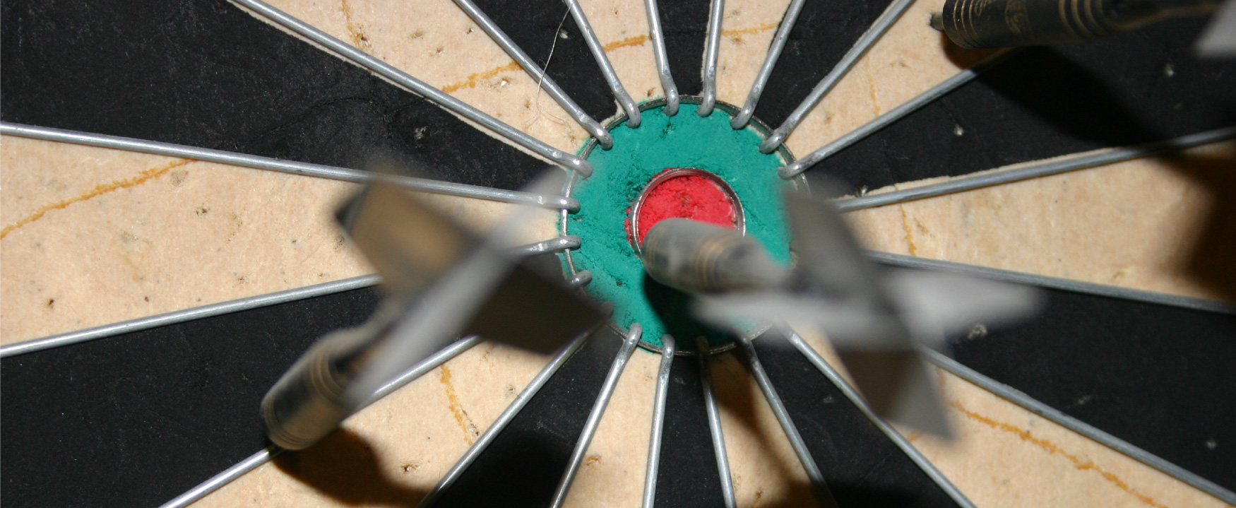 A photograph shows a dart board with a few darts stuck to the board, on is sticking into the bullseye.