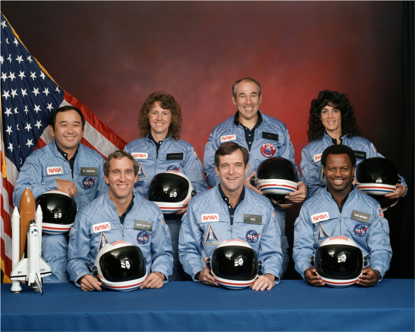 The seven members of the Challenger flight crew pose in their astronaut jackets and hold their helmets. An American flag is behind them. A model of the space shuttle and booster rocket sits on a table in front of them.