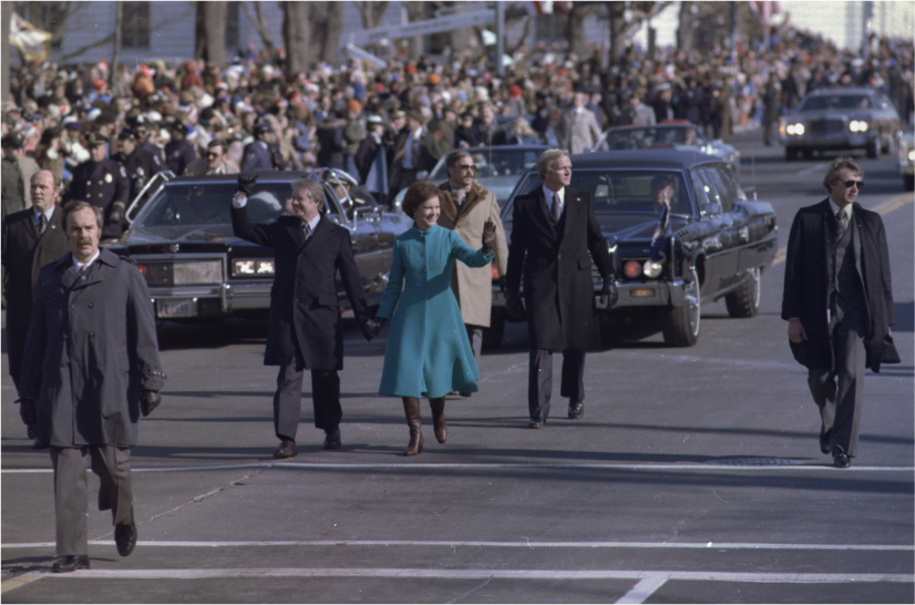 Jimmy Carter and his wife walk on the street in a parade. Cars follow them. A crowd lines the side of the street.