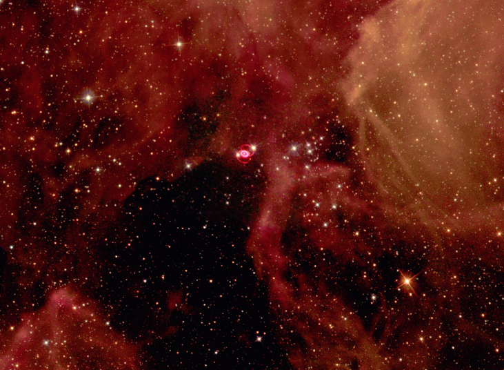 Hubble Space Telescope image of SN 1987A. Large clouds of reddish gas and numerous background stars are seen in this wide-field image of SN 1987A. The supernova remnant is the small, bright red oval near center, connected to two fainter red arcs of light above and below the bright oval.