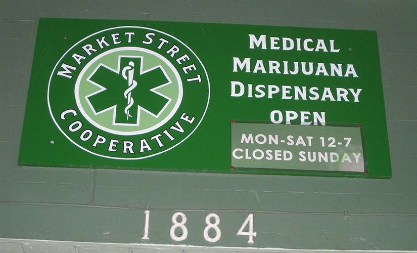 Photo of a sign for a medical marijuana dispensary showing that the business is open