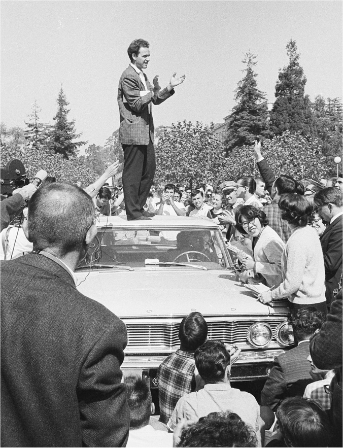Mario Savio stands on top of a car, above the crowd that surrounds him. He appears to be clapping.