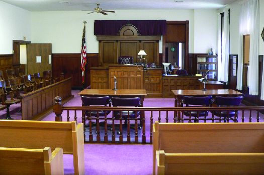 A photo of a typical courtroom, empty of people. In the foreground are benches for attendees, then two tables in the center for the defense and prosecution, and in the background the judge's stand. To the left of the judge's stand is a row of chairs for the jury, and to the right of the judge's stand is the witness stand.