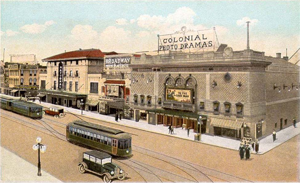 Two cars and two interurbans travel on a downtown road. The downtown strip includes Colonial Photo Dramas and a Broadway Playhouse. People walk on the sidewalks.