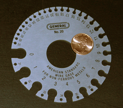 Picture is a photograph of a device used for measuring the gauge of electrical wire. The higher gauge numbers indicate thinner wires.