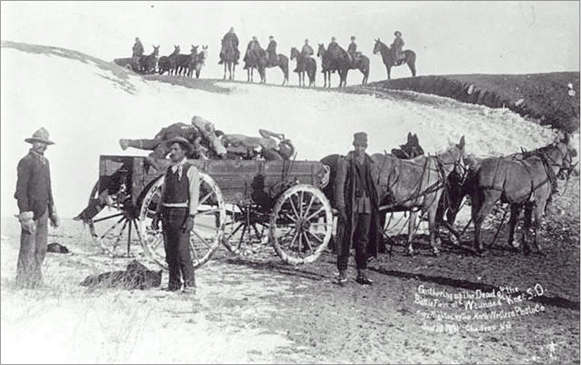 Men stand in front of a wagon that holds a pile of bodies in the foreground. Men on horses and another wagon are in the background.