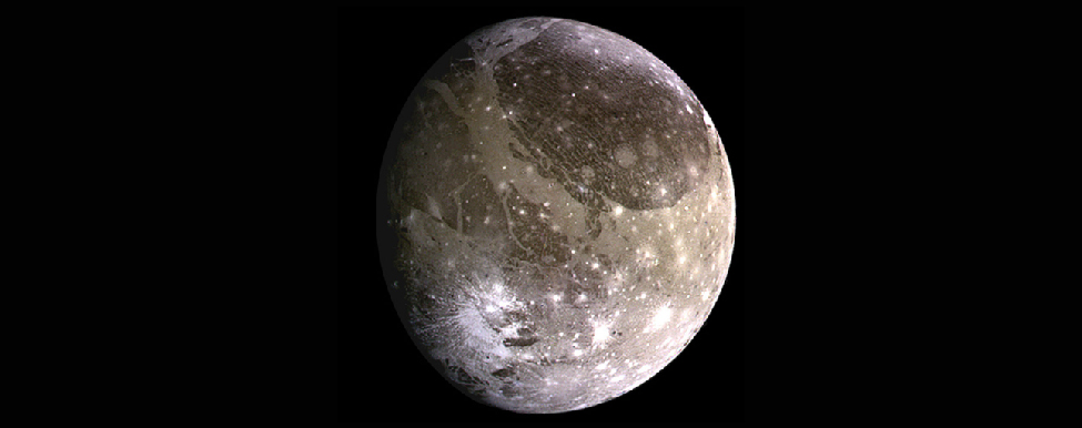 Photograph of Jupiter's moon Ganymede. This image shows nearly the entire disk of Ganymede. The surface is covered with brown and gray rocky areas, and many craters that are nearly the same color as the surface. Below and to the right of center are many bright, rayed craters due to recent impacts that have exposed fresh ice from below the surface.