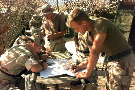 Members of the U.S. military are shown in the field filling out questionnaires.