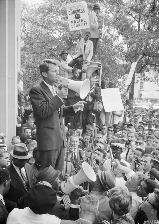 Robert Kennedy uses a megaphone to address a crowd of African Americans and whites. One man in the crowd holds a sign that reads