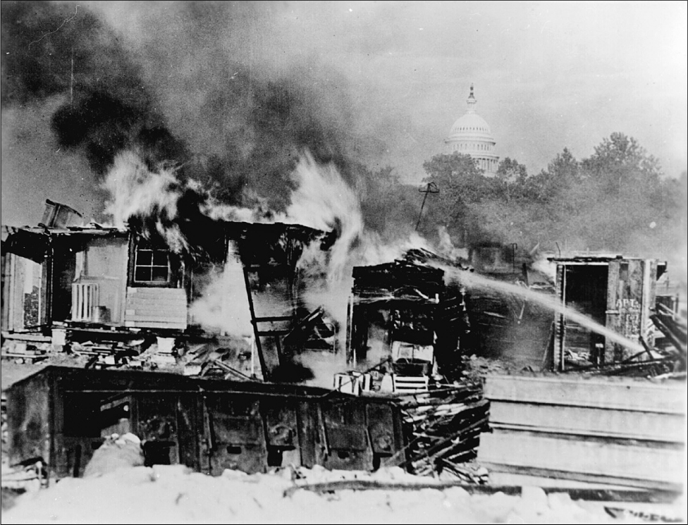 A water hose sprays towards a dilapidated building. Flames and smoke rise from it. The dome of the Capitol building is in the background.