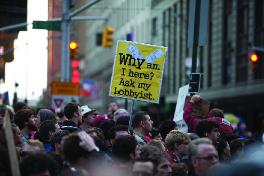 "An image of a crowd of people, one of whom holds a sign that reads ""Why am I here? Ask my lobbyist""."