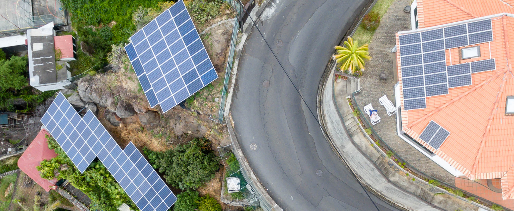 An aerial photograph shows houses on a tropical hillside with solar panels on their roofs.